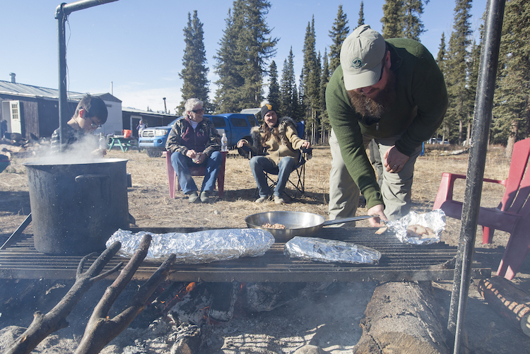 Tom Buzzell keeps an eye on a feast of moose meat, salmon and beaver tail.