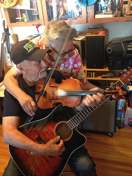 Angus and Dorothy Beaulieu practise their trick. Each have one hand on the fiddle, one on the guitar, and try and play both instruments together. Photo Shannon Graf