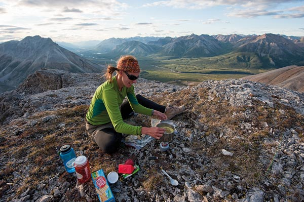 Terri Cairns cooks dinner atop a mountain looking over the Yukon's Snake River, one of the most popular paddling routes in the Peel. Photo Peter Mather