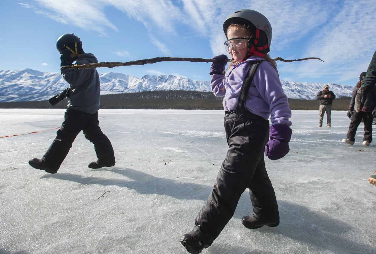 "Amirah Miller-Hundrup walks with a ""safety stick"" on Pickhandle Lake after learning how to check if ice is safe by stabbing it with a hard object."