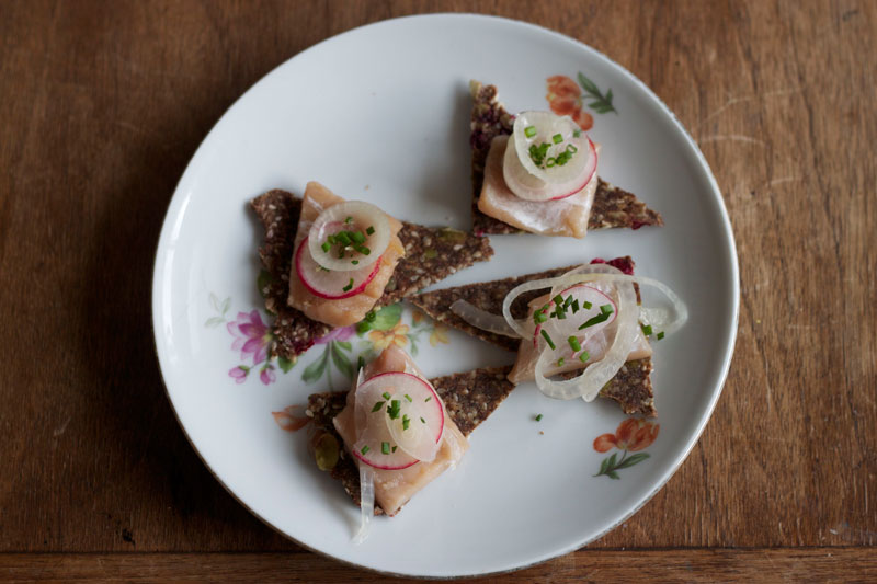 Cranberry rosemary flax crackers with pickled burbot. Recipe and photo by Amy Lam