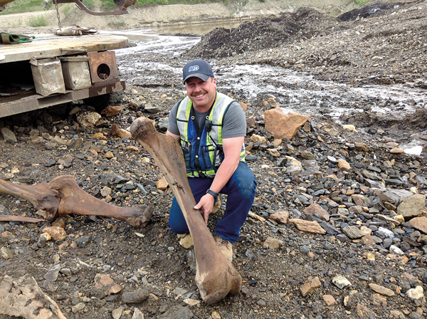 Placer miner Guy Favron holds a woolly mammoth femur found along Last Chance Creek. Photo courtesy of Government of Yukon