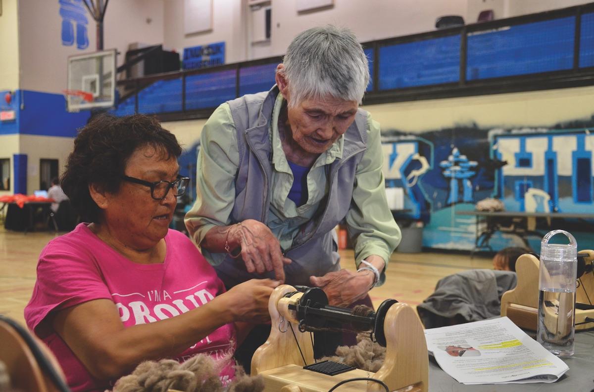 Rankin Inlet artist Helen Iguptak teaches Annie Petaulassie how to spin qiviut fibres into yarn. UP HERE/BETH BROWN