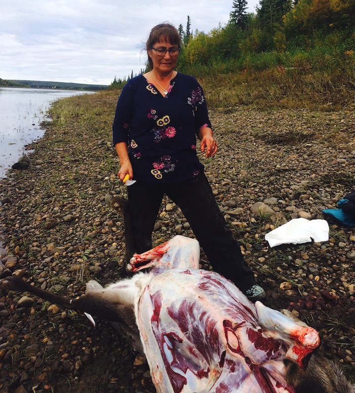 Kassi skins a caribou along the shore of the Porcupine River.