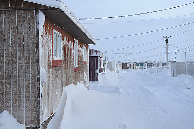 A line of houses on a snowy road. Photo by Herb Mathisen