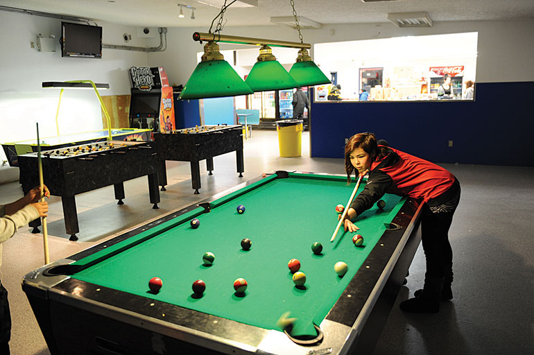 Suki Hogaluk, 16, shoots some pool at the Olapkivik Games Hall. Photo by Herb Mathisen