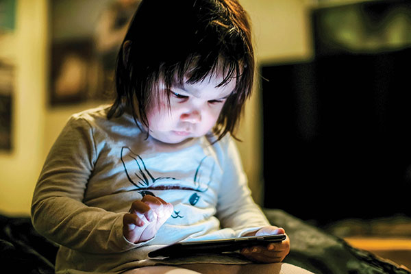 Two-year-old Sarah opens an app on a cell phone in Arviat. CREDIT PAUL ANINGAT