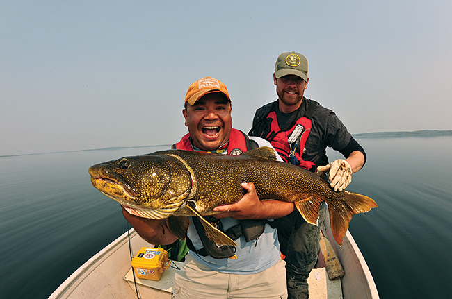 Anglers show off a hefty lake trout on a calm day in the Northwest  Territories.