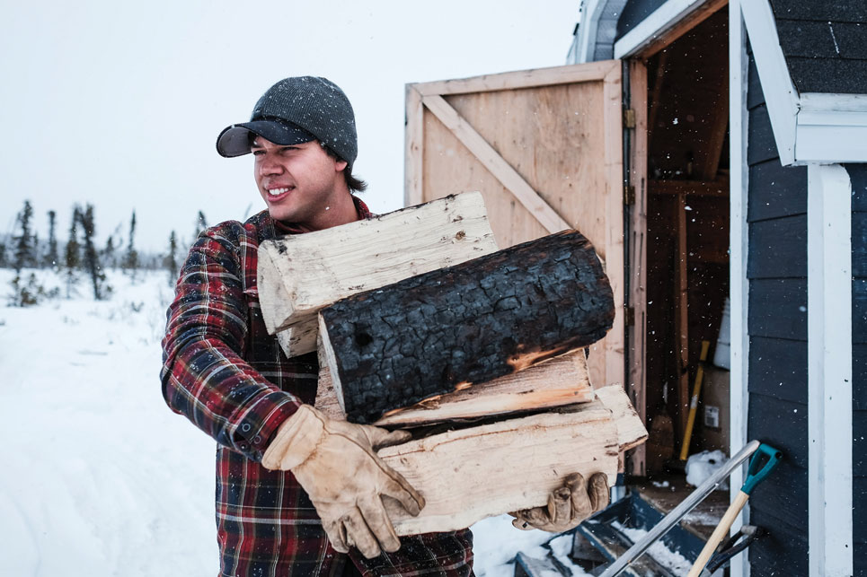 Matt Lavoie stocks his woodpile at his Airport Lake cabin. Photo by Weronika Murray