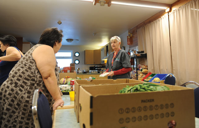 Margaret Cochrane, manager of the emergency shelter, sorts through boxes of goods from the city's Food Rescue program. The bread, fruits, vegetables and other perishables go a long way for residents of the building's downstairs suites. Photo Herb Mathisen