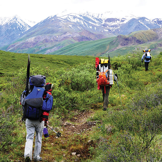 CARRYING YOUR BOAT UP AN OLD KLUANE HORSE TRAIL. Photo courtesy of Paul Burbidge.