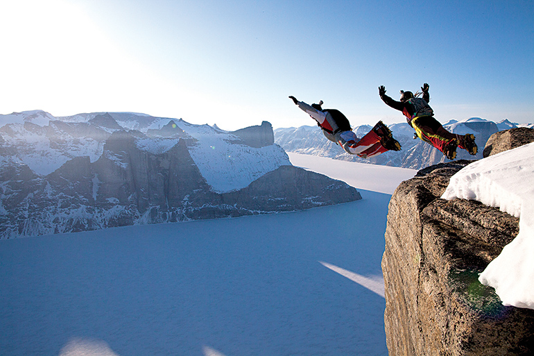 Dressed in track suits, Australians Carly Thomas and Wildman Shovel (yes, that's really his name) jump the lower exit of the 1,300-metre Ottawa Peak over Sam Ford Fiord.