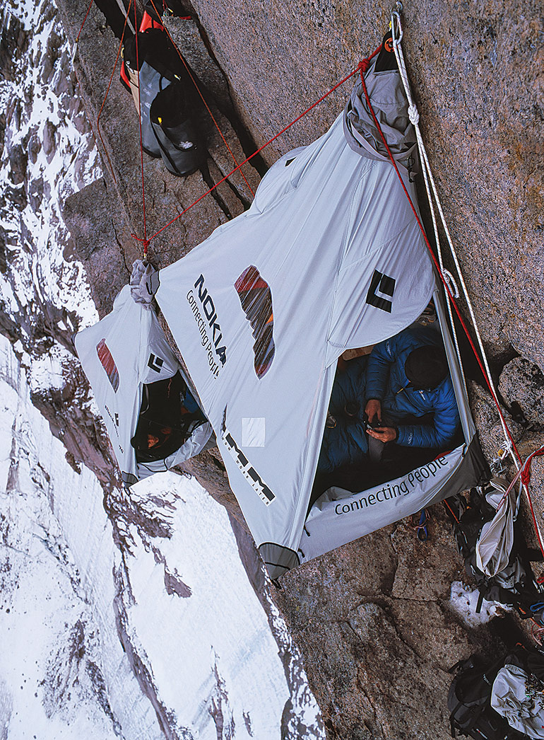A portaledge (portable ledge) camp at 4,900 feet, almost halfway up Asgard's north face. Campers sleeping in these hanging, canvas-covered cots are strapped in with a harness attached to the rock wall.