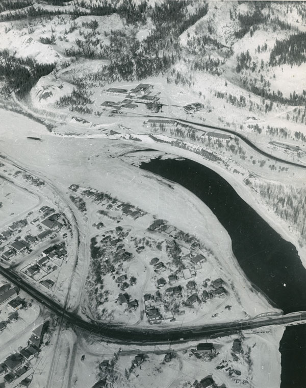An aerial shot of Whiskey Flats and the surrounding area. The Whitehorse General Hospital sits above the river, while on the lower bank the houses of Whiskey Flats are scattered across what's now Rotary Park. (Yukon Archives/Whitehorse Star Ltd.)