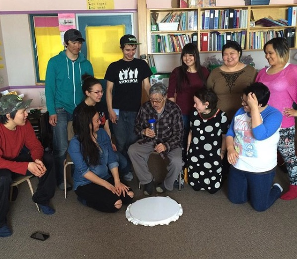 Charlie Panigoniak singing and playing the drum with Nunavut students in 2016. CREDIT IVAMUSICINC