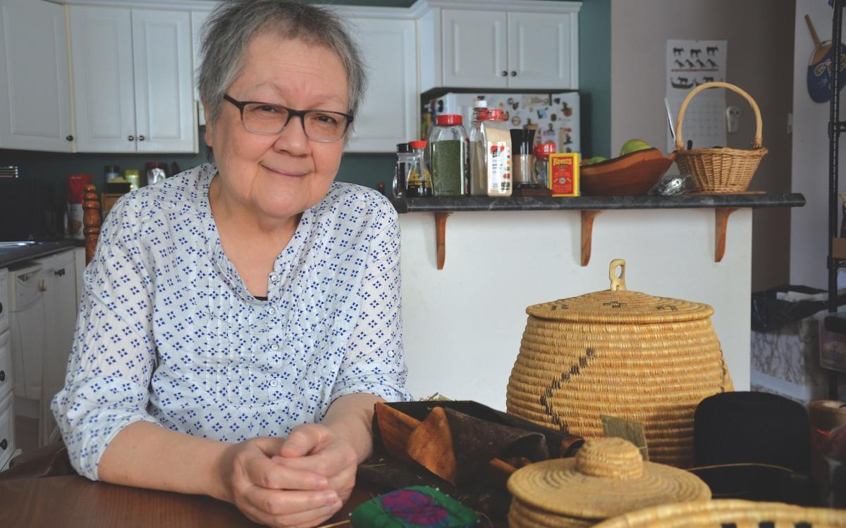 Margaret Lawrence at home in her kitchen, surrounded by some of her hand-sewn grass baskets.