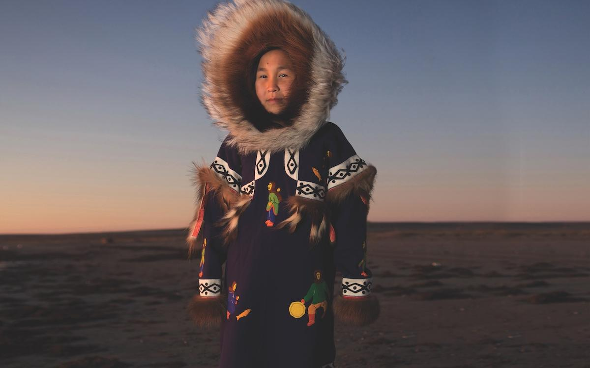 CARMELLA KLENGENBERG WEARS HER GRANDMOTHER'S DRUM-DANCING PARKA, MADE FROM STROUD, WITH WOLVERINE TRIM AND A WOLF SUNBURST PATTERN LINING THE HOOD. THE RED DYE ON THE UNDERSIDE OF THE FRINGES WAS BELIEVED TO BRING GOOD LUCK AND IS A DETAIL STILL SEEN ON PARKAS TODAY.