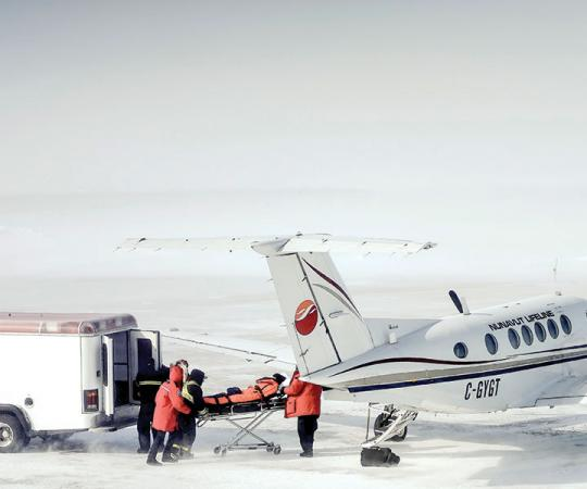 Nunavut Lifeline: Medics rush a patient in Arviat onto a King Air 200 for a medevac to Manitoba before a winter storm hits. Photo by Paul Aningat.
