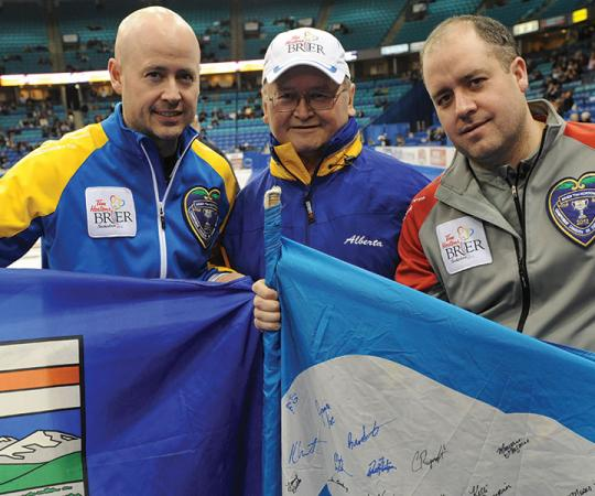 Kevin Koe, left, and Jamie Koe, right, pose with their father Fred at the Brier in Saskatoon in 2012, when the two brothers faced off in the playoffs.