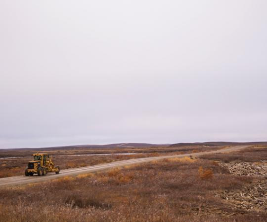 Pingos dot the landscape along the road winding south out of Tuktoyaktuk. Ryan Yakeleya, an E. Gruben's employee, drives a grader toward the Tuk-Inuvik highway worksite. Photo by Angela Gzowski