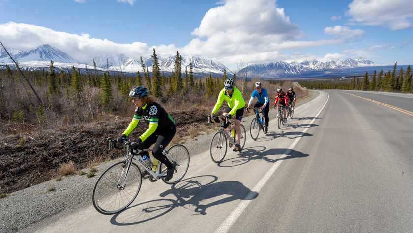 Cyclists pass the St. Elias Mountains in Kluane National Park. Photo by Joel Krahn