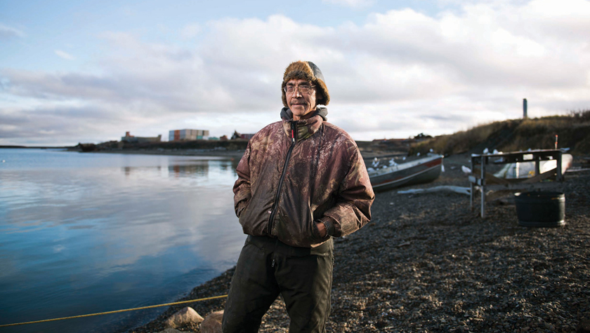Wayne Cockney stands by his fishnet on the shore of the Beaufort Sea. Photo by Angela Gzowski